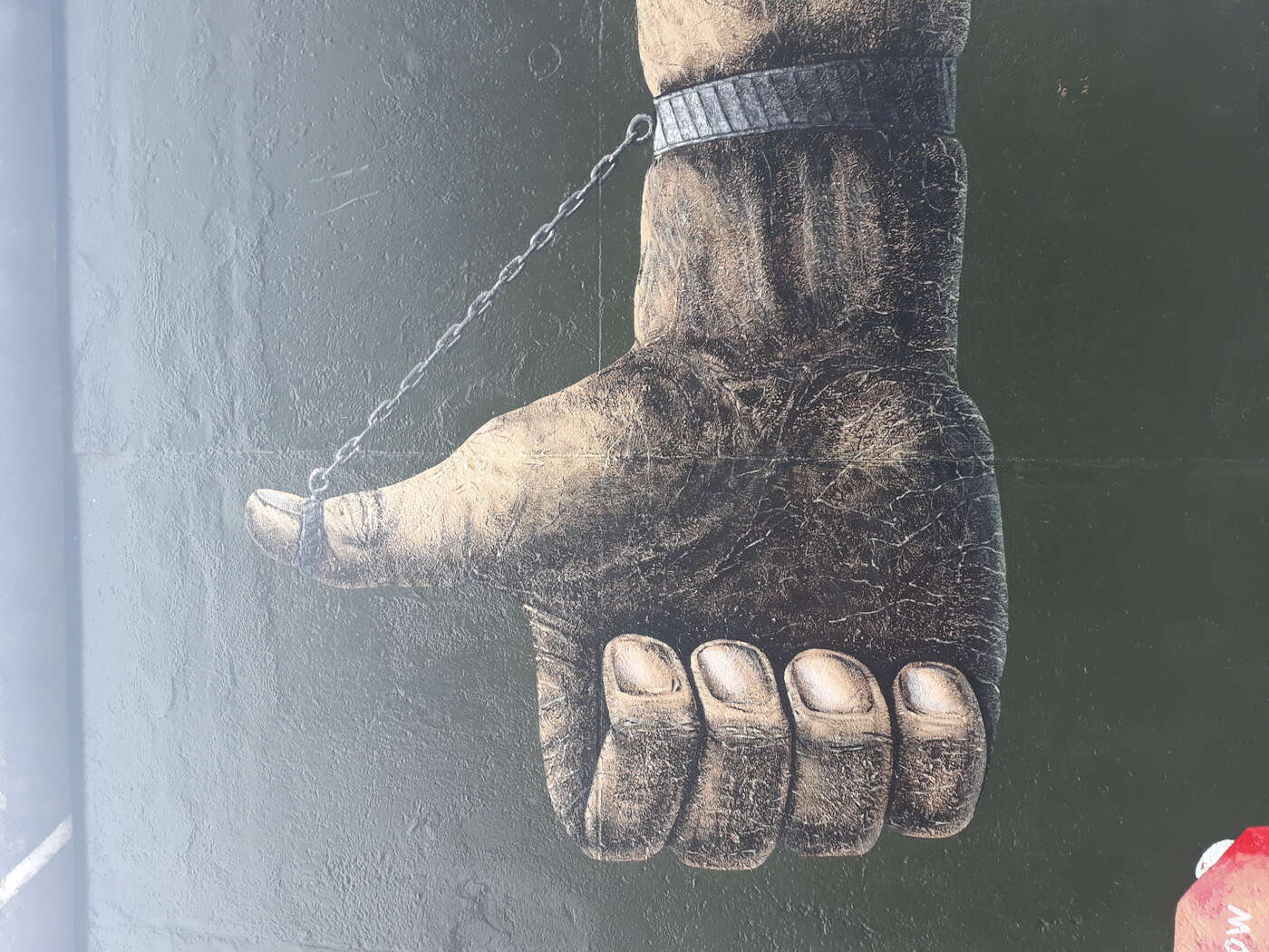 An image taken of streetart at the Berlin Wall.  The art portrays a forced thumbs up.