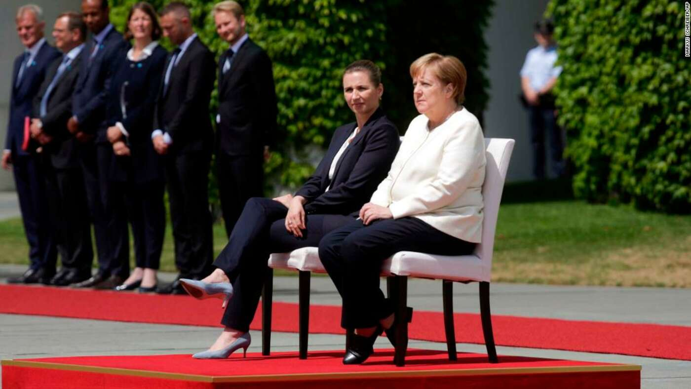 "Angela Merkel pictured seated during the national anthem, following a series of public ""shaking attacks""."